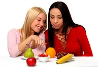 Two girls looking at the fruits on the table with one pointing at it