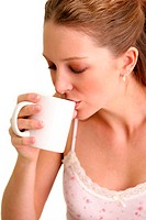 A woman drinking from a white cup