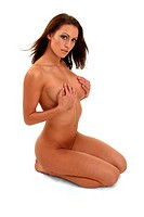 A naked woman kneeling down with her hands covering her breasts