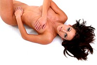 A woman lying naked on the floor with her hands covering her private parts
