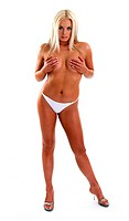 A topless woman in white panties covering her breasts with her hands