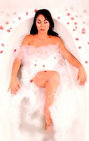 An Asian woman relaxing in a bathtub with rose petals everywhere