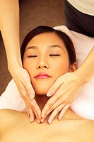 An asian woman lying down with her eyes closed while a pair of hands giving her a facial massage