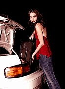 A woman in jeans keeping her luggage into a car boot