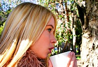 A blonde hair girl drinking at the woods