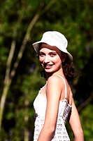 A woman in white dress and white hat smiling at the camera
