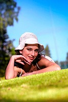 A woman with a white hat posing by lying on the grass (thumbnail)
