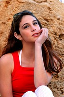 A girl in red sleeveless top resting her chin on her palm (thumbnail)