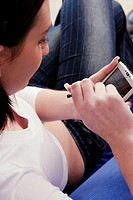 A woman sitting down tapping her PDA (thumbnail)