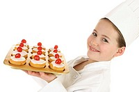 A boy disguising as a chef holding a tray of cakes