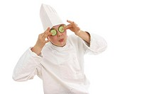 A boy disguising as a chef placing two pieces of cucumber on his eyes