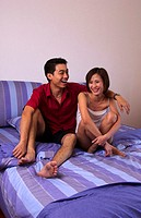 Couple sitting on the bed laughing