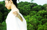 Side shot of woman in white against a greenery background