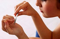 Woman shaping her fingernails with a fingernail file (thumbnail)