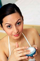 Woman in white bra holding a whitening cream