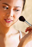 Woman applying some blusher on her cheek