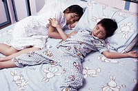 Boy and girl sleeping on the bed