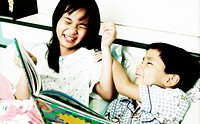 Boy and girl playing while reading book