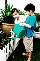 Boy and girl watering the plants