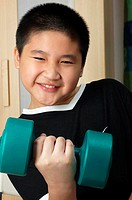 Boy lifting up a dumb bell