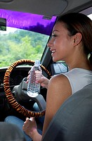 Woman drinking water in the car