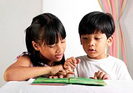 Boy and girl sharing a book