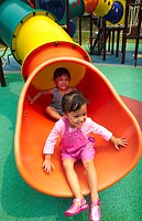 Girls sliding down a slide