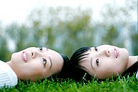 Two women lying on the grass.