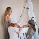 Children admiring a baby in a crib