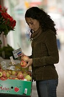 Young woman buying apples on outdoors market