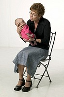 Grandmother sitting in studio, holding baby girl