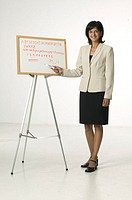 Female teacher standing pointing to text on whiteboard, posing in studio, portrait