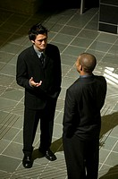 Two businessmen talking, indoors, elevated view