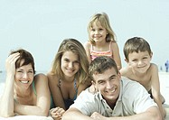 Family lying on beach, smiling, portrait