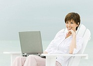 Woman sitting in deckchair using laptop, sea in background
