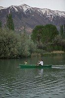 Two people in canoe on river, by mountains