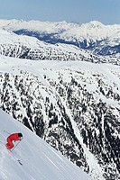 Lone heli-skier atop mountain, British Columbia, Canada, elevated view