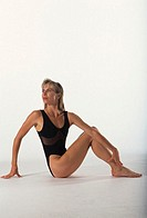 Fit woman sitting on floor stretching body