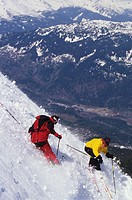 Two skiers carving down steep slope, Whistler Mount, British Columbia, Canada, elevated view