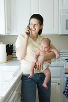 Woman on telephone holding baby boy (0-3 months) in domestic kitchen