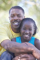 Father hugging daughter (9-11), holding basketball, smiling, portrait