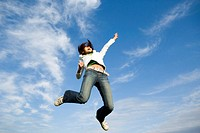 Young woman jumping into air, reaching up, low angle view