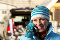Mature woman wearing winter clothes, talking on mobile phone