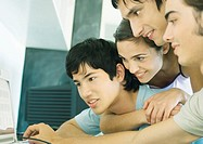 Four young adult friends looking at computer screen together