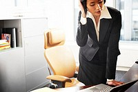 Businesswoman leaning on desk, hand on head