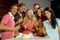 Young woman cutting birthday cake, friends holding champagne, portrait