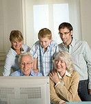 Family using computer, boy (6-8) leaning on grandparent´s shoulders