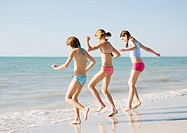 Three girls running toward water on beach