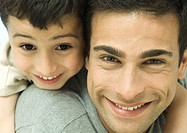 Father and son smiling, close-up of faces