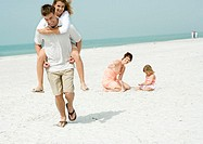 Father carrying teenage daughter piggyback on beach while mother watches